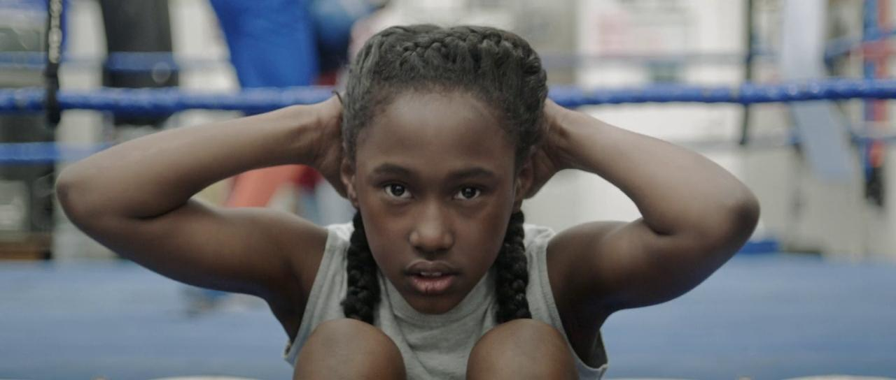 screencap from the fits movie with lead character facing camera while doing pull up exercise